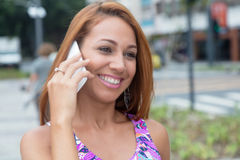 Extraordinary woman with red hair laughing at phone Stock Photos