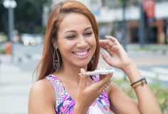 Extraordinary woman with red hair sending voice message at phone. Outdoors in the city royalty free stock photography