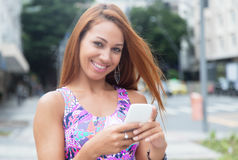 Extraordinary woman with red hair typing message at phone Royalty Free Stock Image