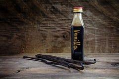 Extrato de baunilha, caseiro em uma garrafa pequena e em feijões de baunilha sobre imagens de stock royalty free