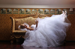 Extravagant bride on sofa, holding a glass of wine Stock Photo