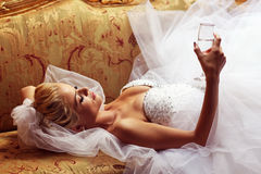 Extravagant bride on sofa, holding a glass of wine Royalty Free Stock Photos