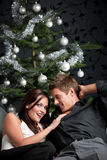 Extravagant couple in front of Christmas tree Royalty Free Stock Photos