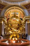 Extravagant golden sculpture in the lobby of a famous hotel in Las Vegas. Las Vegas, NV, USA - 13th July 2013: People walking around the lobby fountain famous stock photo