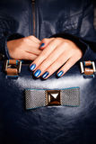 Extravagant nail polished hands on a bag Stock Photography