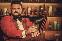 Extravagant stylish man with whisky glass sitting on armchair in Stock Images