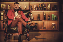 Extravagant stylish man with whisky glass sitting on armchair in Stock Photos