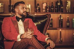 Extravagant stylish man with whisky glass sitting on armchair in Stock Photo