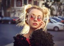 Extravagantes blondes Mädchen in den rosafarbenen Gläsern Stockfoto
