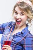 Extrem überraschte kaukasische blonde Frau in überprüftem Hemd roten Juice Using Straw trinkend Lizenzfreies Stockfoto