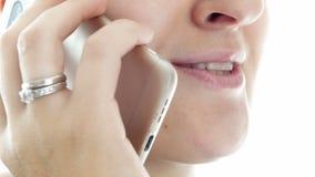 Extrem closeupvideo av den unga kvinnan som talar, genom telefonen och att le
