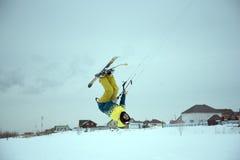 Extrem fristil skidar hoppet med den unga mannen på vintersäsongen snowkiting Arkivbild