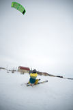 Extrem fristil skidar hoppet med den unga mannen på vintersäsongen snowkiting Arkivfoto