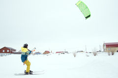 Extrem fristil skidar hoppet med den unga mannen på vintersäsongen snowkiting Arkivfoton