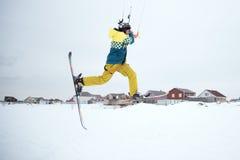 Extrem fristil skidar hoppet med den unga mannen på vintersäsongen snowkiting Royaltyfri Fotografi