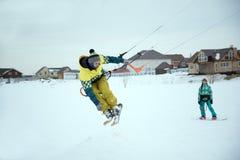 Extrem fristil skidar hoppet med den unga mannen på vintersäsongen snowkiting Royaltyfri Bild