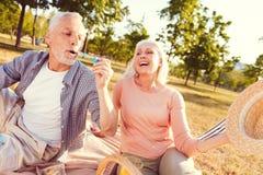 Extrem glückliche Frau, die Schlagseifenblasen des Ehemanns betrachtet stockbild