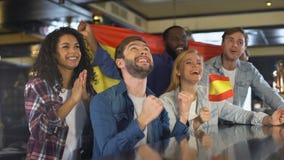 Extrem glückliche spanische Anhänger, welche die Staatsflagge, Sieg feiernd wellenartig bewegen stock video footage