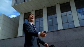 Extrem glücklicher Büroangestellter, der Förderung, gute Nachrichten vom Telefon feiert lizenzfreies stockbild