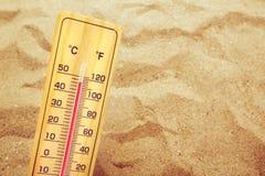 Extrem hohe Temperaturen, Thermometer auf warmem Wüstensand stockfotos