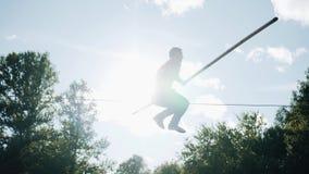 Extrem idrottsman nen som hoppar på ett rep ovanför jordningen Mycket kall längd i fot räknat Stor kapacitet arkivfilmer