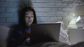 Extrem müde asiatische Frau, die an Laptop nachts im Schlafzimmer, Workaholic arbeitet stock footage