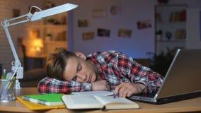 Extrem müder Student, der durch Tabelle auf Stapel von Büchern, überbelasteter Schüler schläft stock footage