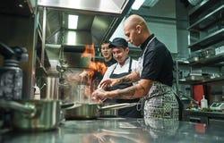 Extrem matlagning Profesional kock som undervisar hans två unga deltagare i utbildning hur hur till flambemat säkert Restaurangkö fotografering för bildbyråer