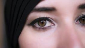 Extrem n?rbild av en ung mitt - ?stlig muslim kvinna i svart hijab som ?ppnar bruna ?gon och ser till kameran lager videofilmer
