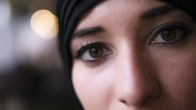 Extrem n?rbild av en ung mitt - ?stlig muslimsk kvinna i svart hijab som ?ppnar ?gon f?r m?rk brunt och ser till kameran lager videofilmer