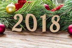 Extrem nettes Makro- des neuen Jahres 2018, Kieferhintergrund mit Weihnachtsbällen und Rot beugt auf dem Holztisch Lizenzfreie Stockfotos