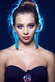 Extrem schönes junges Mädchen mit den ausdrucksvollen blauen Augen, die blaue Quastenohrringe, Babyhaar glänzt in der Hintergrund lizenzfreie stockfotos