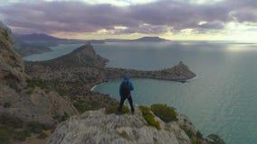 Extrem schneller Brummenflug über dem Bergsteigermann, der auf Felsen bei Sonnenaufgang steht Schattenbild des kauernden Geschäft stock footage