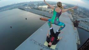 Extrem sport, kvinnlig som överst balanserar på manben av bron, farlig hobby arkivfilmer