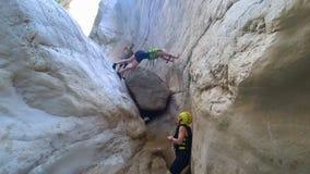 Extremal sport, en grupp av turister i special kläder för en aktiv hobby att övervinna en farlig klättring i en grotta under stock video