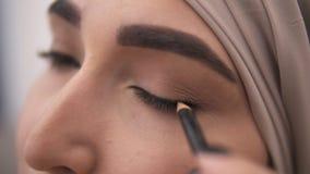 Extremamente próximo acima da opinião uma mulher muçulmana nova que faz uma seta em sua pálpebra usando o eyepencil preto Aturdir video estoque