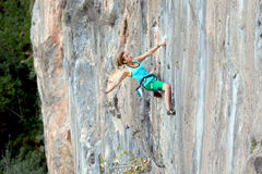 Extreme Athlete on rocky Wall makes relaxed elegant Move Stock Photos