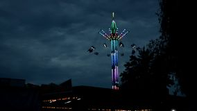 Extreme attraction in amusement park,Attraction carousel on a long stock, multi-colored with light bulbs in dark time. Attraction carousel on a long stock, multi stock video footage