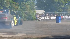 Extreme auto competition, car performs drift on fenced area on fenced area in front of people. Kiev, Ukraine 23 May 2018: extreme auto competition, car performs stock video
