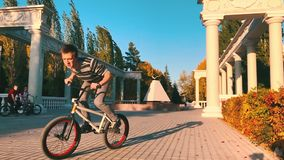 Bmx bikers jumping on bicycles in a sunny park in the summer. The young biker bmx makes ollie-tricks and rides a bicycle. Extreme bikers stand with a magnificent stock video footage