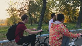 Extreme bikers stand with a magnificent bmx in a sunny summer park, they ride at sunset. stock footage