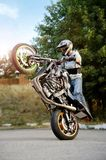 Extreme biking stunt performer practicing tricks on the road. Ivano-Frankivsk, Ukraine - 28 August 2015 : Confident biker performing extreme stunts on sport royalty free stock images