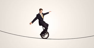 Extreme business man riding unicycle on a rope. Concept on background stock image