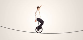 Extreme business man riding unicycle on a rope. Concept on background Stock Photography