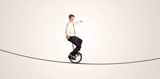 Extreme business man riding unicycle on a rope. Concept on background Royalty Free Stock Image