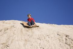 Extreme Childhood Fun. A young kid sliding down sand dunes Royalty Free Stock Images