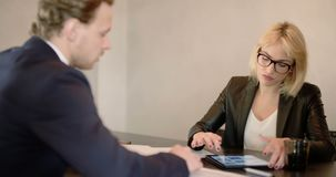 Extreme close up of business woman using tablet computer on a meeting. Businesswoman Discussing With Male Colleague Over Digital Tablet in office. Business stock video footage