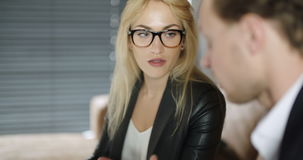 Extreme close up of business woman using tablet computer on a meeting. Businesswoman Discussing With Male Colleague Over Digital Tablet in office. Business stock footage