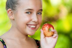 Face shot of cute girl holding red apple. Stock Photos