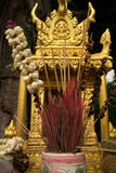 Extreme close up detail of a gold spirit house in Southeast Asia, with incense and flowers at center (vertical) Stock Photo